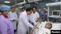 中国总理李克强在湖北省监利县一家医院与一位受伤的女乘客交谈。