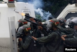 Riot police fire tear gas while clashing with opposition supporters rallying against President Nicolas Maduro in Caracas, Venezuela, May 3, 2017.