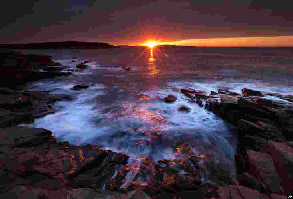 The sun's rays strike the rocky coast of Acadia National Park, in Maine, USA.