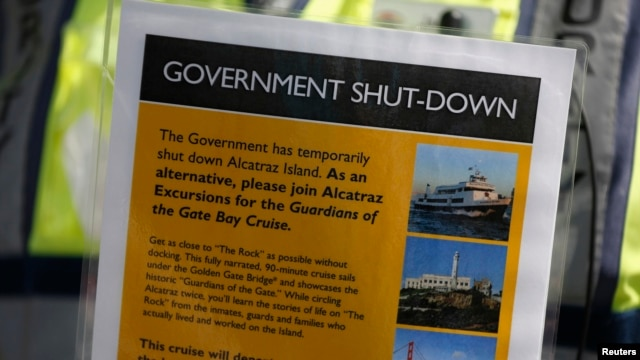 Security officer Jarvis Landlum holds a sign informing people on the government shutdown of Alcatraz Island, a tourist attraction operated by the National Park Service, in San Francisco, California Oct. 1, 2013.