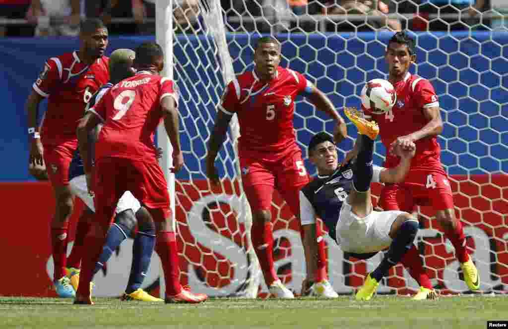 El delantero de Estados Unidos, Joe Corona, intenta disparar al arco rodeado por defensores de camisetas rojas de Panamá durante el partido final jugado en Chicago.