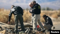 Investigators from the National Transportation Safety Board (NTSB) look at wreckage from the crash of Virgin Galactic's SpaceShipTwo near Cantil, California, Nov. 2, 2014.