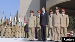 President Bashar al-Assad stands with his military generals, most of whom are Alawites, at the Tomb of the Unknown Soldier in Damascus, October 6, 2011