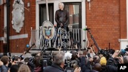 FILE - WikiLeaks founder Julian Assange stands on the balcony of the Ecuadorian embassy, prior to speaking, in London, May 19, 2017.