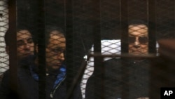 Ousted Egyptian President Hosni Mubarak, 86, lies on a journey, next to his son Gamal, second left, in the defendants cage, during a court hearing in Cairo, Egypt, Saturday, Nov. 29, 2014.