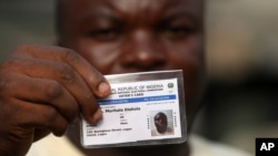 File- Muritala Diekola, displays his voters registration card in Lagos, Nigeria.