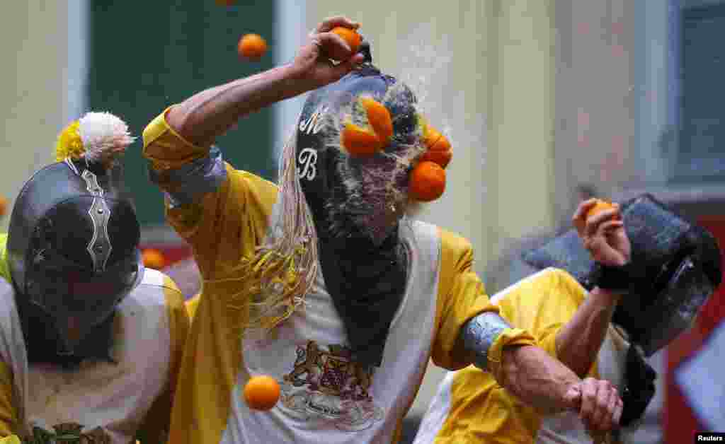 A participant is hit by an orange during an annual carnival battle in the northern Italian town of Ivrea, Italy.