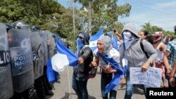 A demonstrator shouts slogans to riot police during a protest against Nicaraguan President Daniel Ortega's government in Managua, Nicaragua September 23, 2018.