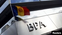 FILE - An Andorran national flag flies next to a Banca Privada d'Andorra (BPA) office in Andorra la Vella, March 29, 2015.