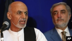 FILE - Afghan presidential candidate Ashraf Ghani Ahmadzai, left, speaks as another candidate Abdullah Abdullah listens during a joint press conference in Kabul, Afghanistan, Aug. 8, 2014.