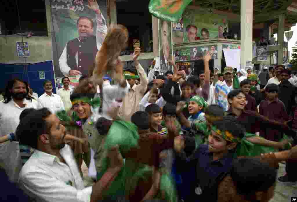 Supporters of Pakistan's former Prime Minister Nawaz Sharif celebrate after initial results from parliamentary elections put his party in the lead, Islamabad, May 12, 2013.