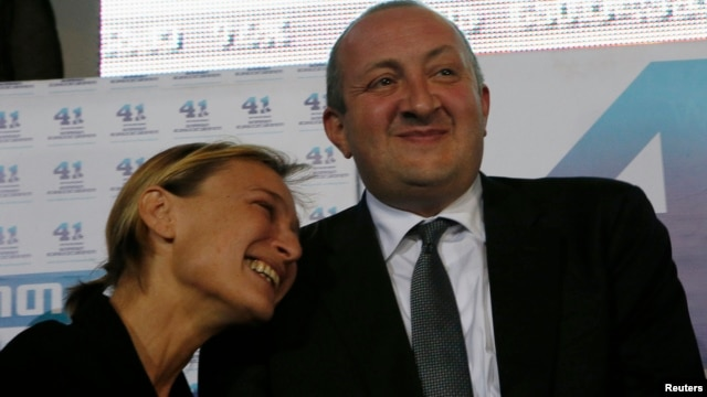 Frontrunner Giorgi Margvelashvili (R) is seen with his partner, Maka Chichua, at the Georgian Dream coalition's headquarters in Tbilisi, October 27, 2013.