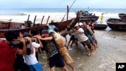 Ngư dân tỉnh Quảng Nam đẩy một tàu đánh cá vào bờ. Tàu bè các tỉnh duyên hải từ miền Trung trở ra đã được khuyến cáo trở lại đất liền.