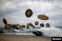 FILE - Amphibious assault vehicles of the South Korean Marine Corps fire smoke bombs as they come ashore during a U.S.-South Korea joint landing operation drill as a part of the two countries' annual military training called Foal Eagle, in Pohang, South Korea, April 2, 2017.