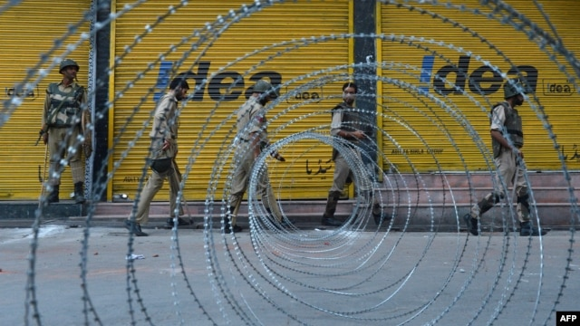 Indian paramilitary and police patrol near a barbed wire fence during a curfew imposed on the Kashmiri summer capital in Srinagar on July 19, 2013.