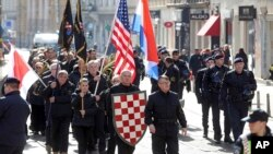 Desničarska povorka maršira centrom Zagreba noseći hrvatsku i američku zastavu i ustaška obeležja (AP Photo)