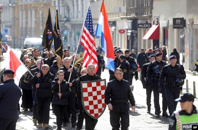 FILE - A group of right-wing radicals wave Croatian and U.S. flags as they march through downtown Zagreb, Feb. 26, 2017.