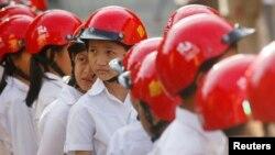 សិស្សកម្ពុជាពាក់មួកសុវត្ថិភាពខណៈពេលដែលពួកគេចូលរួមក្នុងពិធីប្រគល់មួកសុវត្ថិភាពដោយតារាសម្តែងម៉ាឡេស៊ី Michelle Yeoh (មិនស្ថិតនៅក្នុងរូប) នៅក្នុងសាលាបឋមសិក្សាទួលស្វាយព្រៃនៅក្នុងទីក្រុងភ្នំពេញ កាលពីថ្ងៃទី៩ ខែធ្នូ ឆ្នាំ២០១៤។ (រូបភាព REUTERS/Samrang Pring)