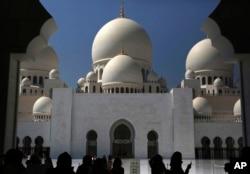 Tourists take photographs at the Sheikh Zayed Grand Mosque in Abu Dhabi, United Arab Emirates, on Sunday, Oct. 23, 2016. (AP Photo/Jon Gambrell)