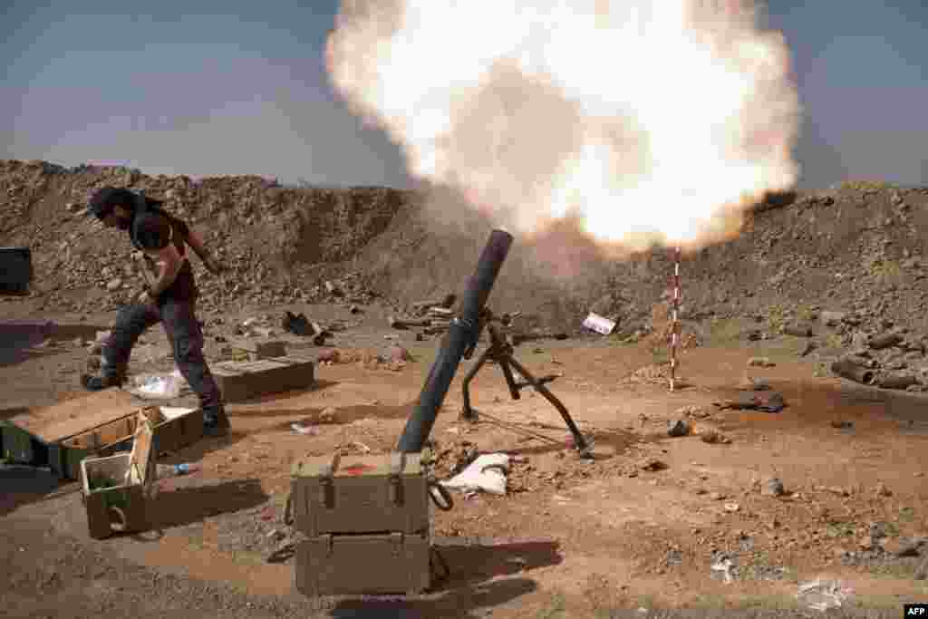 An Iraqi militia fighter from Shi'ite cleric Moqtada al-Sadr's Saraya al-Salam's Peace Brigade, fires a mortar during heavy clashes with Islamic State fighters in Tuz Khurmatu in Salaheddin province about 88 kilometres (55 miles) south of Kirkuk.