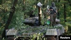 7月16日,一名亲俄罗斯的分离主义者在乌克兰东部的顿涅茨克站在T64坦克上面拍照。