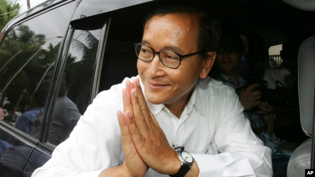 FILE - In this July 27, 2008 photo, Sam Rainsy leader of Sam Rainsy Party greets his supporters after casting his vote at a polling station in kampong Cham province north of  Phnom Penh.