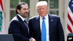 President Donald Trump, right, shakes hands during a joint news conference with Lebanese Prime Minister Saad Hariri in the Rose Garden of the White House, July 25, 2017, in Washington.