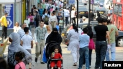 FILE - Shoppers walk in a market in Upton Park, a neighborhood in the British capital's most culturally diverse borough of Newham, in east London June 26, 2010.