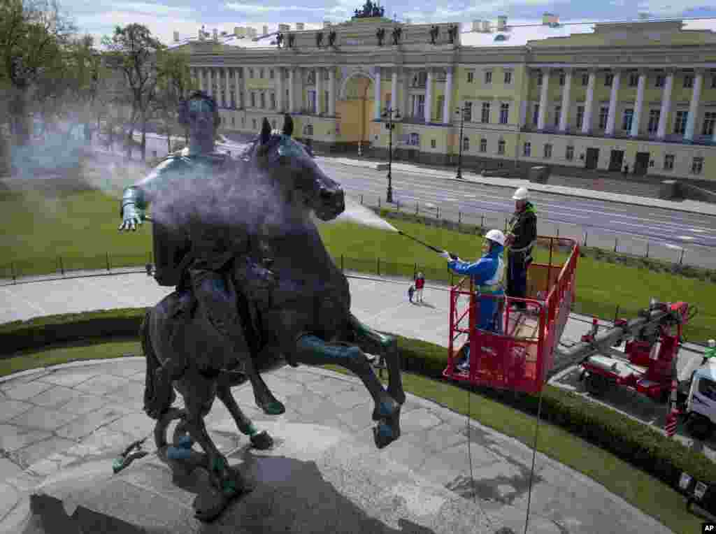 A worker washes a city landmarks, the equestrian statue of Peter the Great known as the Bronze Horseman by French sculptor Etienne Maurice Falconet, in St.Petersburg, Russia.