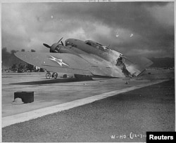 FILE - A burnt B-17C aircraft rests near Hangar Number Five, Hickam Field, following the attack by Japanese aircraft on Pearl Harbor, Hawaii Dec. 7, 1941.