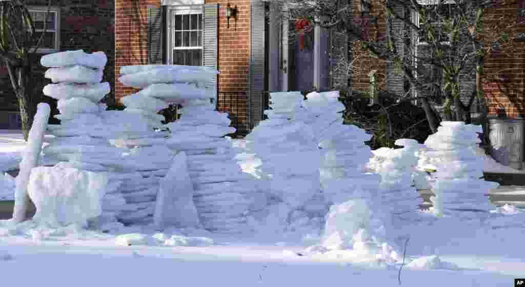 Stacks of icy snow are piled up outside a home after it was removed from a driveway in Cincinnati, Ohio, Feb. 12, 2014.