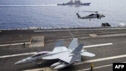 Máy bay chiến đấu F/A-18F Super Hornet và trực thăng SH-60 Seahawk của hải quân Mỹ trên tàu USS George Washington, phía sau là tàu khu trục USS John S. McCain (DDG-56) ngoài khơi bờ biển Việt Nam, tháng 8/2011