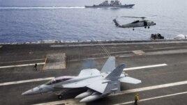 Máy bay chiến đấu F/A-18F Super Hornet và trực thăng SH-60 Seahawk của hải quân Mỹ trên tàu sân bay USS George Washington, phía sau là tàu khu trục USS John S. McCain (DDG-56) ngoài khơi bờ biển Việt Nam, ngày 13/8/2011.
