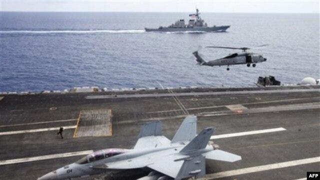Máy bay chiến đấu F/A-18F Super Hornet và trực thăng SH-60 Seahawk của hải quân Mỹ trên tàu sân bay USS George Washington, phía sau là tàu khu trục USS John S. McCain (DDG-56) ngoài khơi bờ biển Việt Nam, ngày 13/8/2011