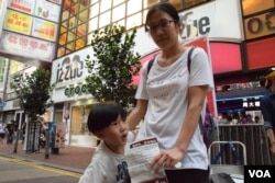 香港市民陸小姐帶同4歲的兒子參觀銅鑼灣的反普教中街頭展覽。(美國之音湯惠芸攝)