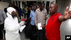 Giới chức y tế đo nhiệt độ của hành khách tại sân bay quốc tế Murtala Muhammed ở Lagos, Nigeria.