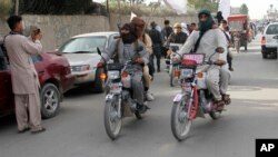 FILE - Taliban fighters ride their motorbikes inside Ghazni city, west of Kabul, Afghanistan, June 16, 2018.