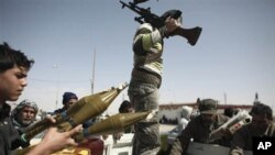 Defected Libyan soldiers and volunteers load weapons onto a truck on the outskirts of the eastern town of Brega, Libya, Thursday, March 3, 2011. Mutinous army units in pickup trucks armed with machine-guns and rocket launchers deployed around the strategi