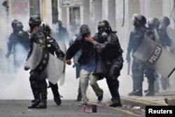 Police help a pedestrian overcome by tear gas as supporters of Salvador Nasralla, presidential candidate for the Opposition Alliance Against the Dictatorship, clash with police during a protest caused by the delayed vote count for the presidential electio