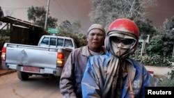 Warga dengan wajah kotor karena abu mengendarai sepeda motor di tengah muntahan abu dari Gunung Sinabung, di desa Sukandebi di Kabupaten Karo, Sumatra Utara (13/6). (Reuters/Antara/Rony Muharman)