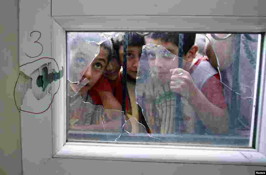 Turkish boys look through a shattered window after an anti-aircraft shell fired from Syria hit a health center across the border in Reyhanli, Hatay province, Turkey, October 23, 2012.