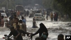 Pakistanis wade through a flooded road caused by heavy monsoon rainfall in Karachi, Pakistan on Saturday, Sept. 10, 2011.