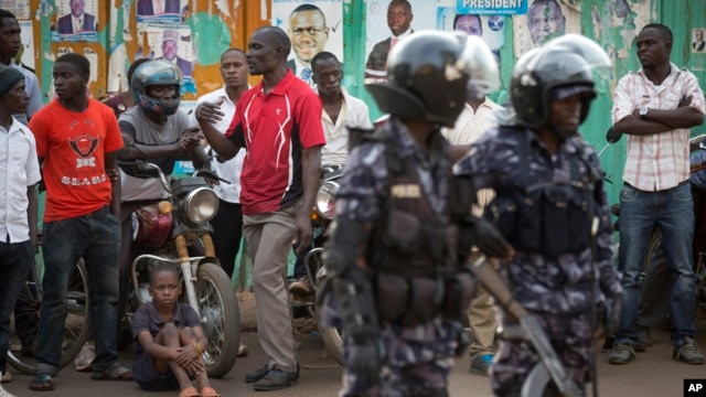 Ugandan riot police stand close to dejected opposition supporters to prevent them from demonstrating, shortly after the election result was announced, in downtown Kampala, Uganda, Feb. 20, 2016.