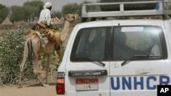 UNHCR convoy passes Sudanese man riding on a camel, Um Shalaya refugee camp south of the Darfur town of Al-Geneina, April 25, 2007 file photo.