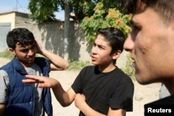 Faisal Grdawe, center, 18, from Syria gestures in front of the National Reception Center For Asylum Seekers in Tirana, Albania, June 6, 2018.