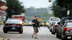 A police officer searches the area after an attack on police headquarters by a gunman in an armored vehicle in Dallas, Texas, June 13, 2015.