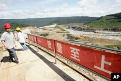 In this Oct. 6, 2012 photo, a Chinese engineer, left, walks by a fence with Chinese slogans reading: Safety first, highest quality and quantity near an entrance of a dam construction site by China National Heavy Machinery Corporation on the Tatay River in Koh Kong province, some 210 kilometers (130 miles) west of Phnom Penh, Cambodia.