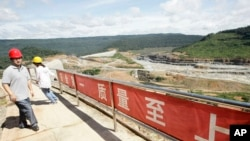 FILE PHOTO- A Chinese engineer, left, walks by a fence with Chinese slogans reading: Safety first, highest quality and quantity near an entrance of a dam construction site by China National Heavy Machinery Corporation on the Tatay River in Koh Kong province.