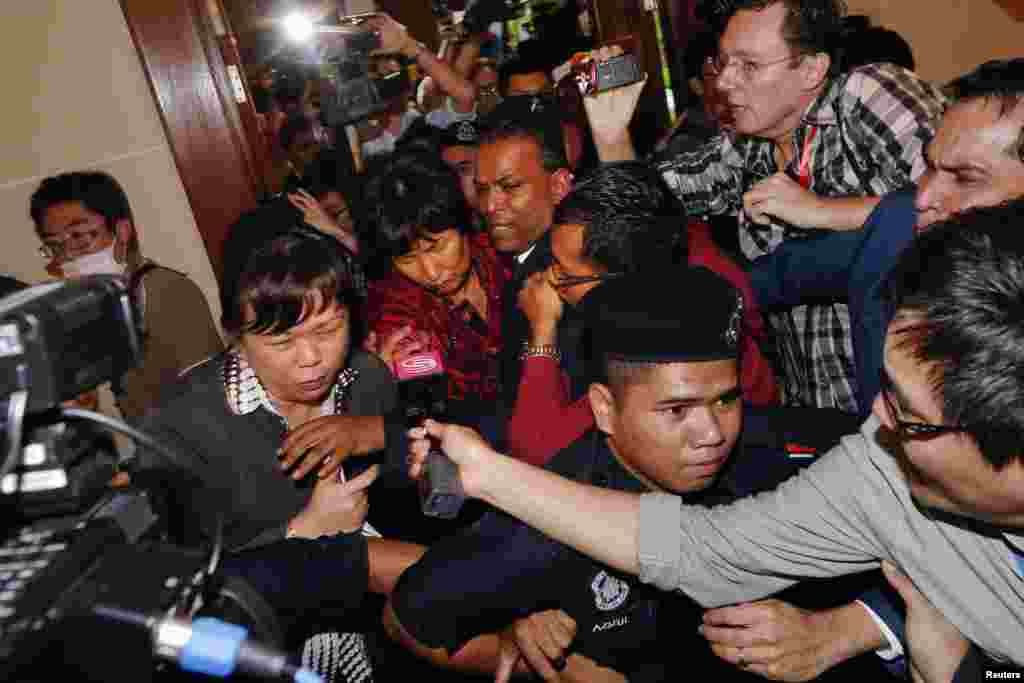 A Chinese family member of a missing Malaysia Airlines MH370 passenger is escorted away from the media outside the media conference area at a hotel near Kuala Lumpur International Airport, March 19, 2014.