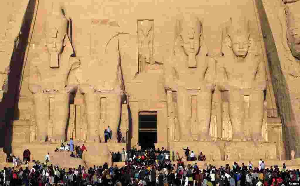 Du khách và khách tham quan xếp hàng bên ngoài đền Abu Simbel tại vùng thượng sông Nile ở Aswan, cách Cairo, Ai Cập khoảng 1265 km về phía nam, để xem nắng ban mai chiếu sáng chính điện bên trong nhân dịp kỷ niệm ngày Pha-ra-ông Ramses Đệ nhị lên ngôi.